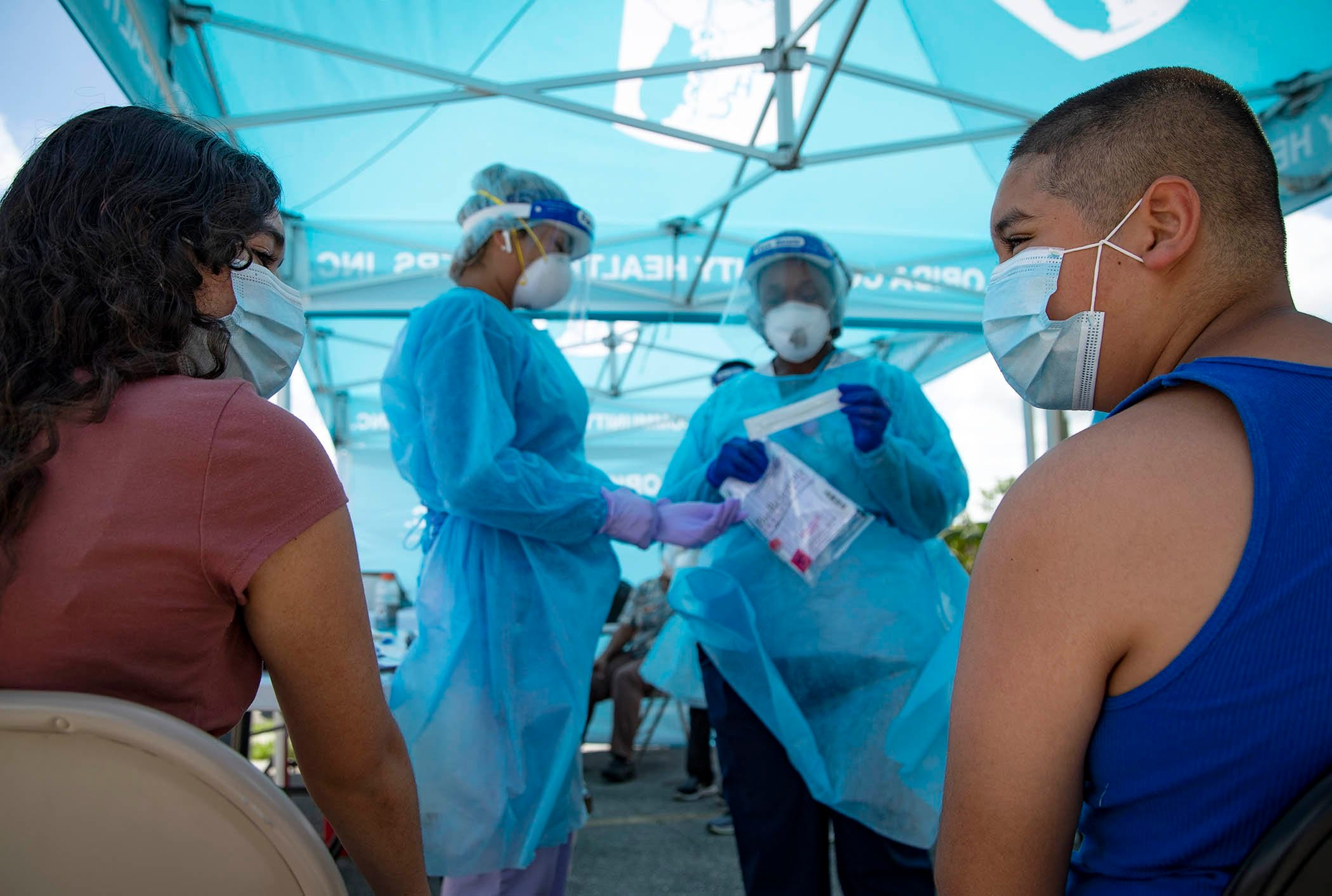 Mayelin Morano, 12, and Ismael Macedo, 10, nervously await a COVID-19 test at a mobile test site run by Florida Community Health Centers in South Bay. The mobile test site is at the food distribution site organized by Tammy Jackson Moore who helped start, the non-profit, Guardians of the Glades. Every Friday she coordinates in one of the tri-city area centers a food distribution and coronavirus testing site. She helped distribute 100,000 pounds of food in South Bay, July 24, 2020.