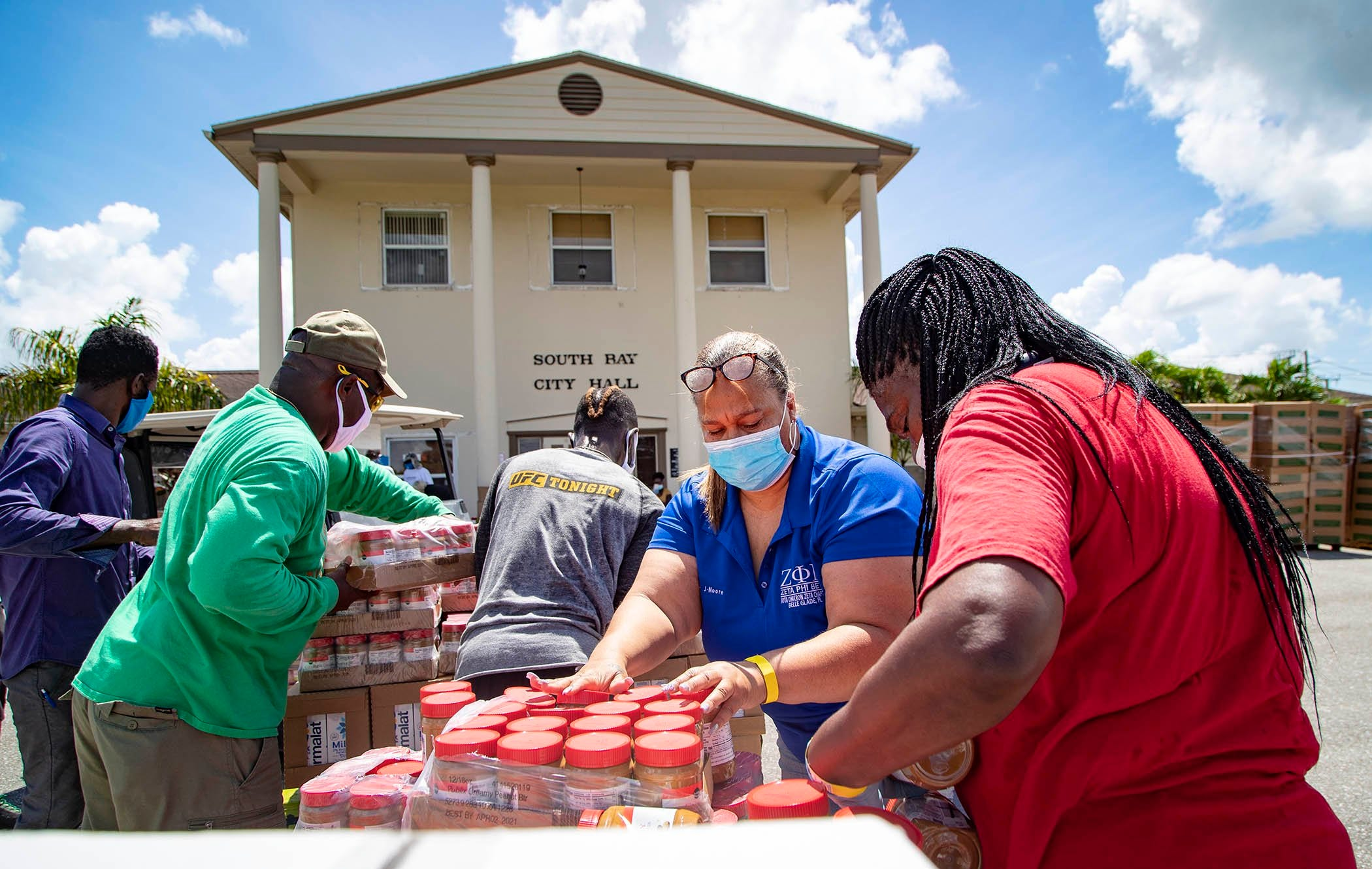 Tammy Jackson Moore (second from right) helped start, the non-profit, Guardians of the Glades. Every Friday she coordinates in one of the tri-city area centers a food distribution and coronavirus testing site. She helped distribute 100,000 pounds of food in South Bay, July 24, 2020.
