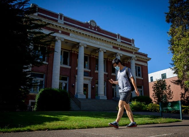 A man walks past Johnson Hall on the University of Oregon campus in Eugene, Oregon on August 26, 2020. The university's administration announced it will hold classes predominantly online and remotely for fall term.