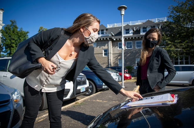Annie Montgomery, left, and Caitlin Plummer, attorneys with Public Defenders Services of Lane County, meet in the parking lot near their closed offices in Eugene. The attorneys have had to change how they work with the clients they represent, including having them sign paperwork on vehicle hoods.