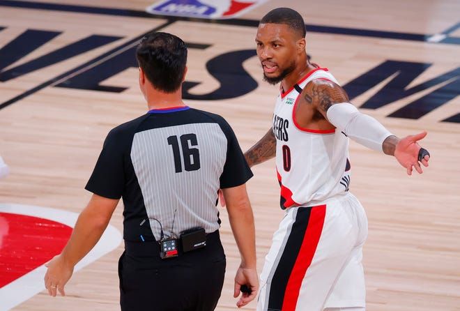 Portland Trail Blazers' Damian Lillard (0) argues with referee David Guthrie (16) during the first quarter of Game 4 of an NBA basketball first-round playoff series against the  Los Angeles Lakers on Monday. Lillard will miss Game 5 on Wednesday with a knee injury. [Kevin C. Cox/Pool Photo via AP]