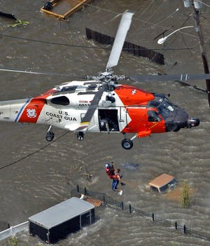 A resident is rescued from the roof of a home by the U.S. Coast Guard as floodwaters from Hurricane Katrina cover the streets Aug. 30, 2005, in New Orleans.