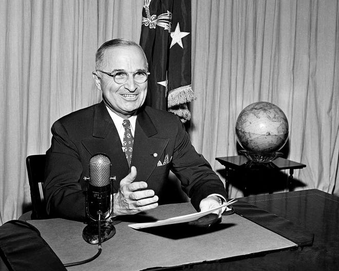 President Harry Truman sits before a microphone at the White House in Washington, where he broadcast a message on the formal surrender of Japan on Sept. 1, 1945.