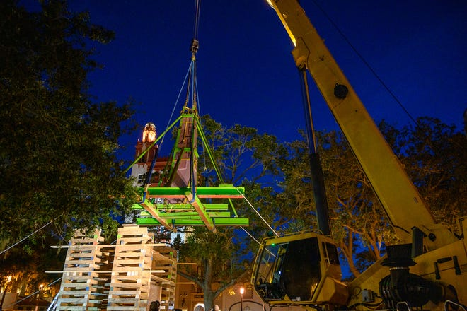 Workers use a crane to remove the top section of the Confederate memorial on the Plaza de la Constitucion in St. Augustine before dawn on Wednesday.