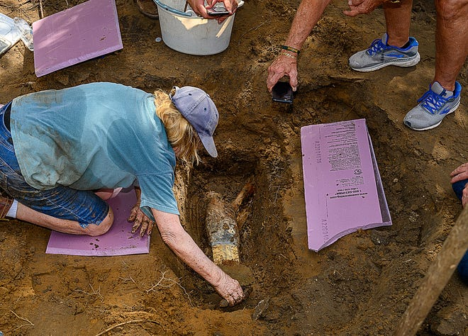 Archaeologist Kathy Deagan searches the soil under the memorial to Confederate Maj. General William Loring on Wednesday after the obelisk was removed from the park behind the Governor's House Cultural Center and Museum in St. Augustine the previous day.