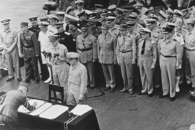 General of the Army Douglas MacArthur, Supreme Allied Commander, and General Wainwright, who surrendered to the Japanese after Bataan and Corregidor, witness the formal Japanese surrender signatures aboard the USS Missouri in Tokyo Bay on Sept. 2, 1945.