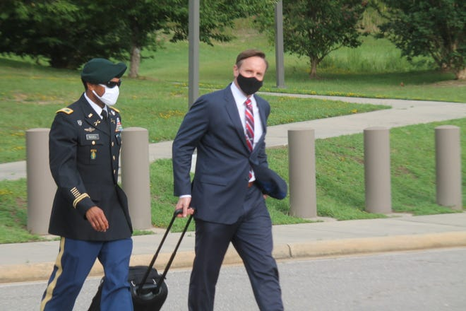 Col. Kevin M. Russell leaves the Fort Bragg courtroom facility with his attorney Michael Waddington, after the first day of his military court-martial Tuesday.