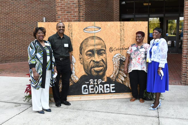 George Floyd's family members pose in front of a mural at a ceremony at Fayetteville State University.  The university held the ceremony to accept the mural for display in Chesnutt library.  Pictured from left are: Dorothy Floyd, his aunt, Roger Floyd, his uncle, Evelyn Simmons, his aunt, and Ruby Floyd, his stepmother.