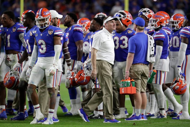 Florida head coach Dan Mullen, center, walks on the field during a time out during the second half of the Orange Bowl NCAA college football game against Virginia, Monday, Dec. 30, 2019, in Miami Gardens, Fla. (AP Photo/Lynne Sladky)