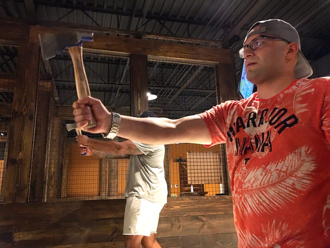 Joel Vara lines his ax up with the target before throwing with his friends at the newly open ax-throwing bar The Hatchetbury in Gainesville on Aug. 19.