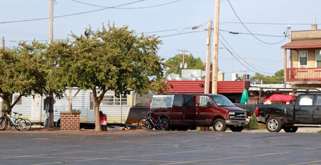 A van and camper occupy parking spaces along North Kalata Place in Appleton. The parking spaces are next to an artesian well.