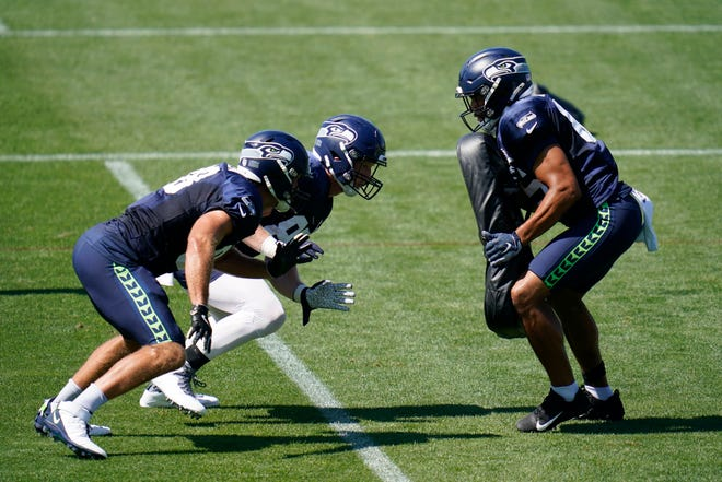 Seattle Seahawks' Greg Olsen, left, and Will Dissly begin to rush toward Tyler Mabry Tuesday, Aug. 18, 2020, during an NFL football training camp in Renton, Wash. (AP Photo/Elaine Thompson)