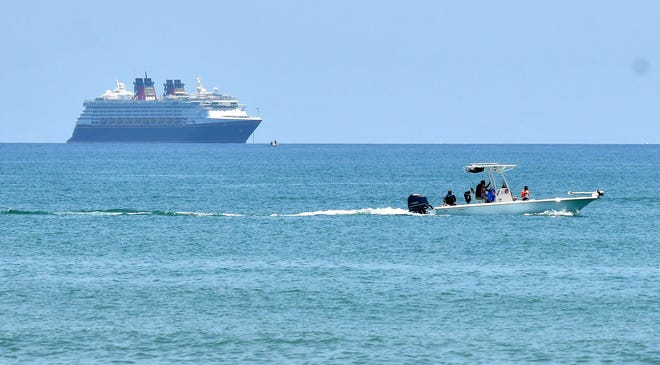 A small passenger boat goes past a Disney cruise ship without passengers offshore near Cocoa Beach. Port Canaveral has not had multiday cruise sailings since mid-March.