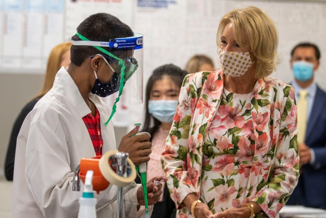 Secretary of Education Betsy DeVos, right, interacts with sophomore Yugeshwar Muralidhar during a visit to a Biotech classroom at Forsyth Central High School in Cumming, Ga., Tuesday, Aug. 25, 2020.