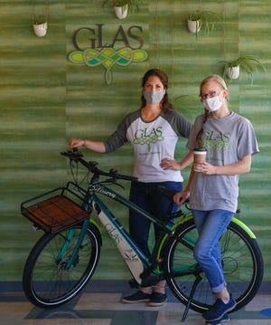 "Glas Coffeehouse Retail Operations Manager Maureen Riordan-Haese, left, and Manager Brenna Panske are pictured with an electric bike that will be used for delivery services to customers. There is a $10 dollar minimum order, including the delivery fee. ""We're going to continue being eco-friendly, providing quality food and drinks to customers and being together for the community,"" Riordan-Haese said."