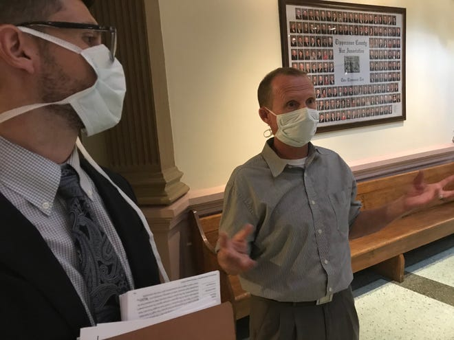 Outside a courtroom at the Tippecanoe County Courthouse, Michael Bryant, a rural West Lafayette man, explains Tuesday, Aug. 25, 2020, why he challenge West Lafayette Mayor John Dennis' executive order mandating the use of masks in public places where social distancing isn't possible during the pandemic. Looking on is his attorney Arie Lipinski. Tippecanoe Circuit Judge Sean Persin said he planned to rule on the case by the end of the week.