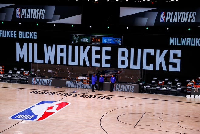 Referees stand on an empty court before the start of a scheduled game between the Milwaukee Bucks and the Orlando Magic for Game 5.