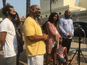 Iesha Harper, center, spoke Wednesday after the Phoenix City Council approved a $475,000 settlement to her family, more than a year after a Phoenix police officer pointed a gun at her fiance during a traffic stop.