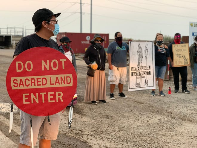 Protesters carried signs against border wall construction in ancestral O'odham lands along the border at a protest in Coolidge on Aug. 26, 2020.