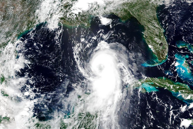 "This Aug.25, 2020, satellite image released by NASA shows Hurricane Laura churning in the Gulf of Mexico. Forecasters say Laura is rapidly intensifying and will become a ""catastrophic"" Category 4 hurricane before landfall. (NASA Worldview, Earth Observing System Data and Information System (EOSDIS) via AP)"