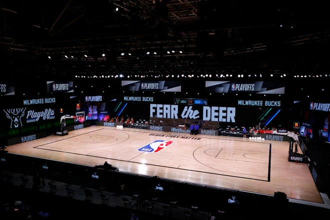 Referees huddle on an empty court at game time of a scheduled game between the Milwaukee Bucks and the Orlando Magic for Game 5 of an NBA basketball first-round playoff series, Wednesday, Aug. 26, 2020, in Lake Buena Vista, Fla.