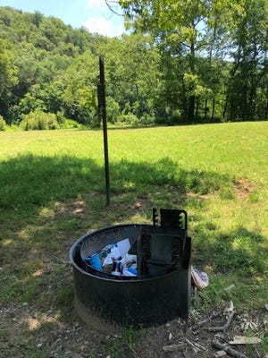 """A campfire ring along the Buffalo River filled with unburned trash was left behind by someone not following the 'Leave no Trace"""" ethic."""