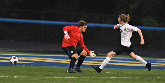 Coshocton's Patrick Shannon hits a shot past Maysville keeper Garrett Frick to tie the game at 2 in a soccer match on Tuesday at Maysville. The game finished as a 2-2 draw.