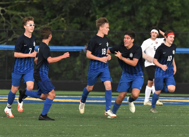 Teammates celebrate a goal by Maysville's Connor Voltz (18) in a soccer match on Tuesday at Maysville. The teams played to a 2-2 draw.