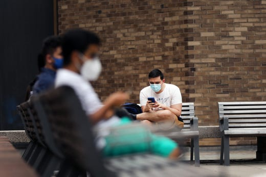 Students at New York University (NYU) wait outside of a Covid-19 test tent outside of its business school on August 25, 2020 in New York City. All students arriving back to the campus are required to get tested for the virus upon arrival, students will then have to be tested again seven to 10 days later.