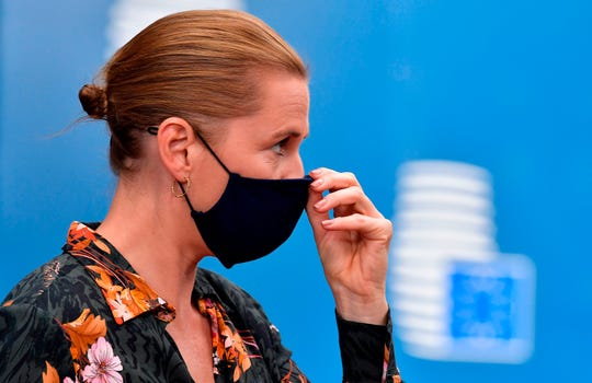 Danish Prime Minister Mette Frederiksen adjusts her face mask as she arrives for a European Union summit on a coronavirus recovery package at the European Council building in Brussels on July 19.