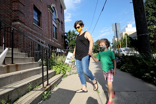 Rebecca Beebe drops her 5-year-old son, Truman, off at childcare at University Avenue Discovery Center in Madison, Wis., Thursday morning, Aug. 13, 2020.