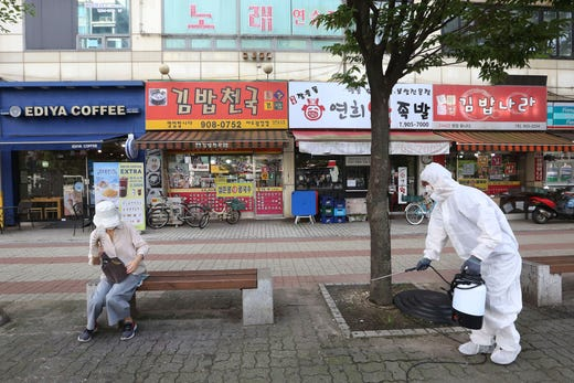A worker disinfects as a precaution against the coronavirus on a street in Goyang, South Korea, Tuesday, Aug. 25, 2020. South Korea is closing schools and switching back to remote learning in the greater capital area as the country counted its 12th straight day of triple-digit daily increases in coronavirus cases.
