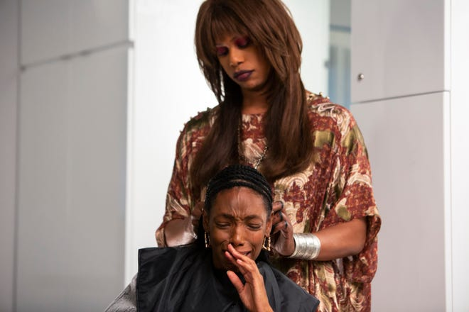 "Virgie (Laverne Cox, standing) gives Anna (Elle Lorraine) a weave that has a mind of its own in the 1989-set horror satire ""Bad Hair."""