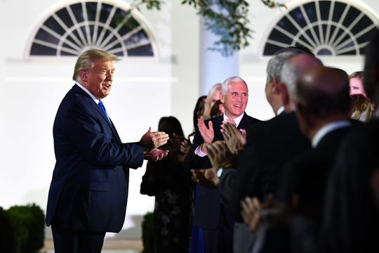 US President Donald Trump, alongside Vice President Mike Pence, arrives to listen to US First Lady Melania Trump address the Republican Convention during its second day from the Rose Garden of the White House August 25, 2020, in Washington, DC.