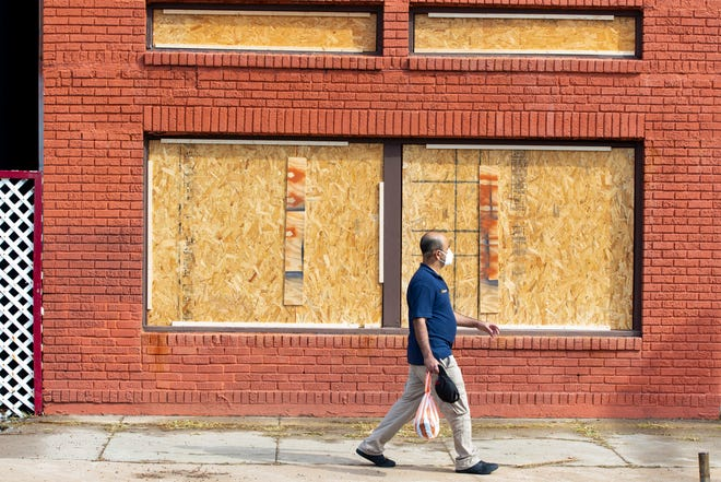 A man on Wednesday, Aug. 25, 2020, walks past a boarded up home in Galveston, TX, as people prepare hours before Hurricane Laura is set to make landfall.