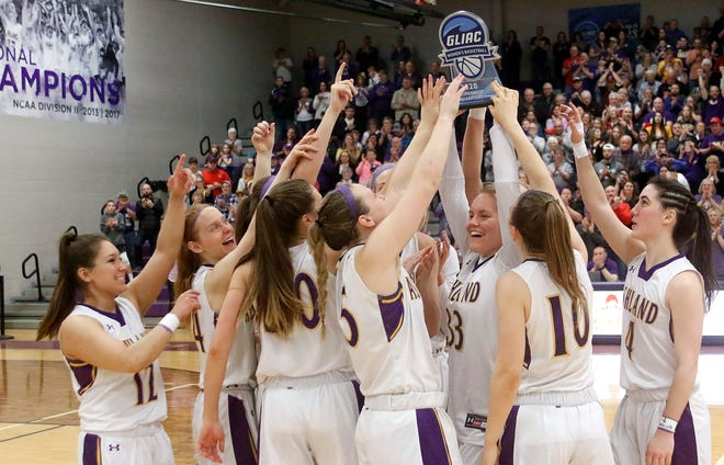 Ashland University's Sarah Hart (33) raises the Great Lakes Intercollegiate Athletic Conference Tournament trophy as she and her teammates celebrate their 61-53 win over Grand Valley State University on March 8, 2020 at Kates Gymnasium.