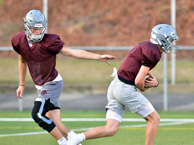 Beaver High School quarterback Brady Hansen hands off the ball to Wyatt Ringer during practice on Aug. 24, 2020.