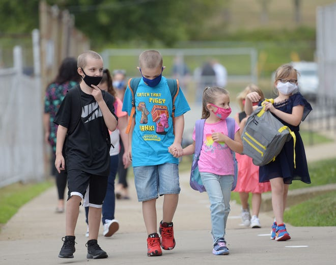 Rochester elementary school children walk  on their first day of school,  Thursday in Rochester.  Some students chose online schooling while the majority of the students are attending in person.