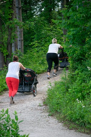 Residents out walking the trail around Memorial Park in Barnesville take in local beauty while pushing their strollers.
