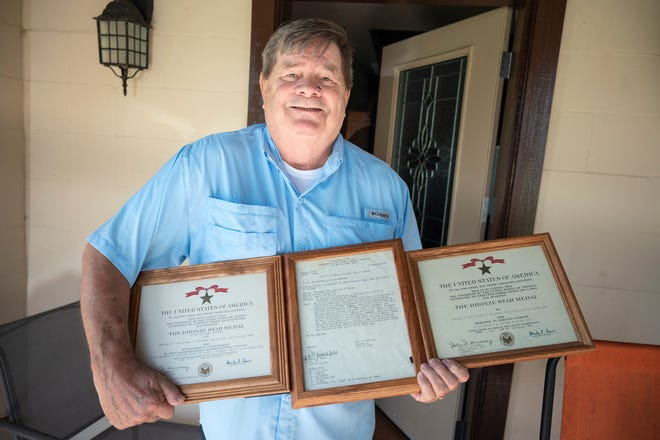 Mike Whitaker holds his awards for his bronze star medals.