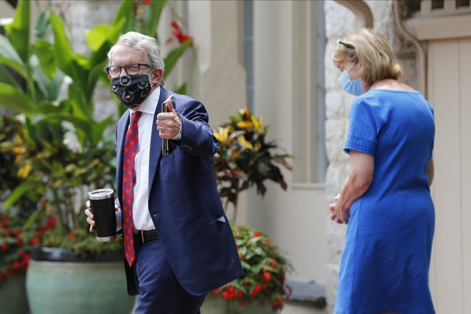 Ohio Governor Mike DeWine, left, and his wife Fran, walk into their residence Thursday, Aug. 6, 2020, in Bexley, Ohio.