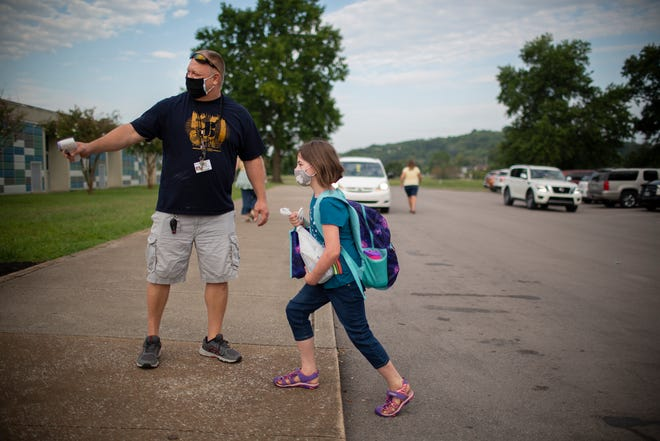 After taking her temperature, physical education teacher Marty Adkison welcomes fourth-grader Paytynn Haines to a new school year at Joseph Brown Elementary School in Columbia, Tenn., on Monday, Aug. 10, 2020. After three weeks of classes, more than 20 students have tested positive for coronavirus.
