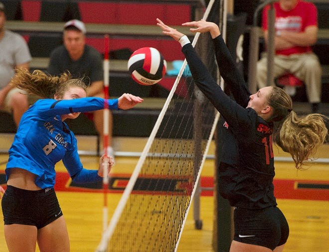 Central Davidson's Madison Tate (right) blocks a hit by Oak Grove's Olivia Stone a volleyball match in the 2019 season.