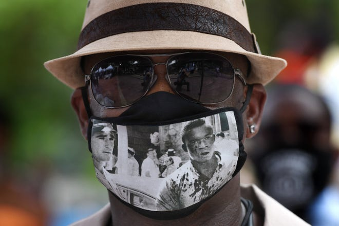 DeVardis Griffin Griffin, the son of Charlie Griffin, wears a mask with the iconic image of his bloodied father from Ax Handle Saturday during Thursday's 60th-anniversary commemoration of Ax Handle Saturday in the newly renamed James Weldon Johnson Park in the heart of downtown Jacksonville. It's where white mobs, many using ax handles as weapons, attacked Black citizens after a series of lunch-counter sit-ins at downtown businesses to try to end the policies of racial segregation.