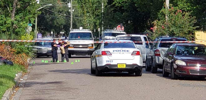 Crime-scene detectives place evidence markers from Thursday's shooting on West Fifth Street.