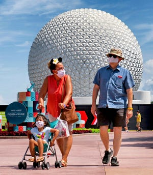 In this July 15, 2020, file photo, guests arrive to attend the official re-opening day of Epcot at Walt Disney World in Lake Buena Vista, Fla. Deputies say a 35-year-old man hit a security guard in the head and threatened to kill him at Epcot theme park when he was asked to follow Disney World's mask rules. An Orange County sheriff's arrest report says Enrico Toro was arrested Aug. 14 on misdemeanor battery charges.