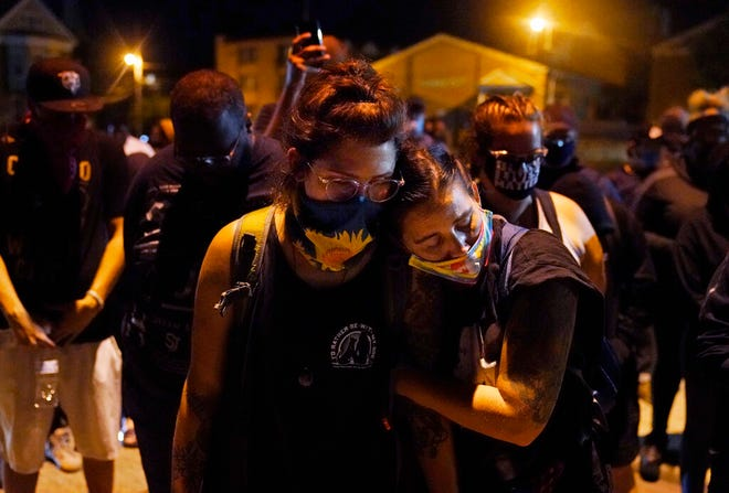 Protesters observe a moment of silence while marching Wednesday night in Kenosha, Wis., near the scene of a fatal shooting Tuesday night. A white, 17-year-old police admirer was arrested Wednesday after two people were shot to death Tuesday during a third straight night of protests in Kenosha over the police shooting of a Black man, Jacob Blake.
