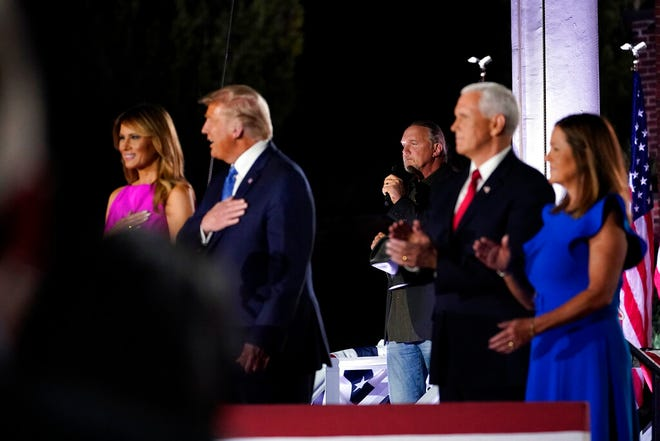 President Donald Trump and first lady Melania Trump stand with Vice President Mike Pence and Karen Pence as Trace Adkins sings the National Anthem on the third day of the Republican National Convention at Fort McHenry National Monument and Historic Shrine in Baltimore, Wednesday.