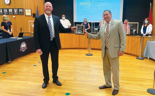 Dale Lynch, right, Tennessee Organization of School Superintendents president-elect, presents a plaque to Oak Ridge Schools Superintendent Bruce Borchers at Monday night's Oak Ridge Board of Education meeting. Borchers was selected as the School Superintendent of the Year for the East Region of the state.