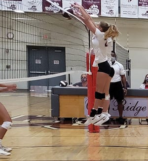 Lady Wildcat senior Brenna Allred goes up for a block in the match against the Lady Rebels.